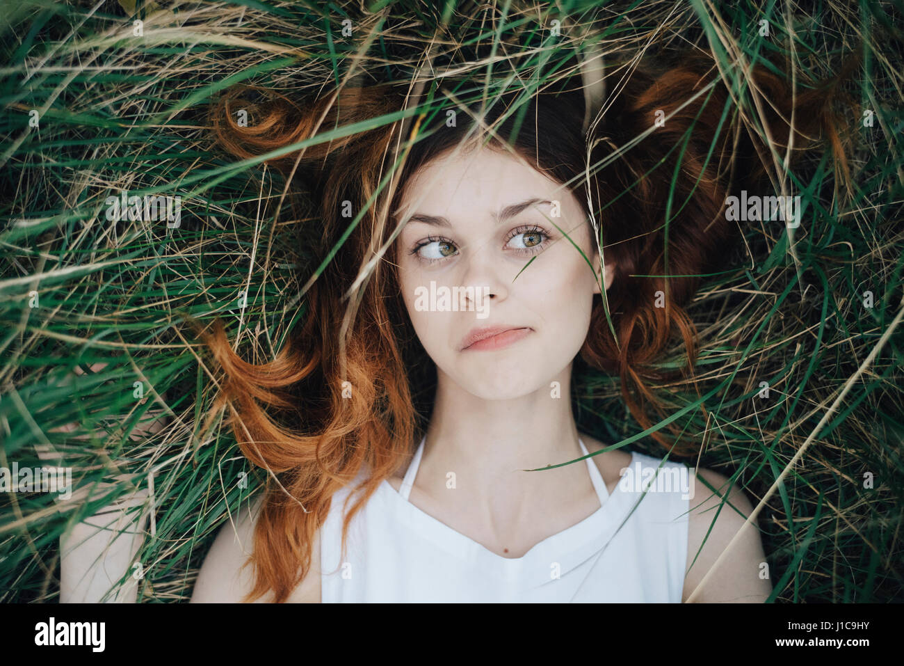 Caucasian woman laying in grass blowing hair off face - Stock Image