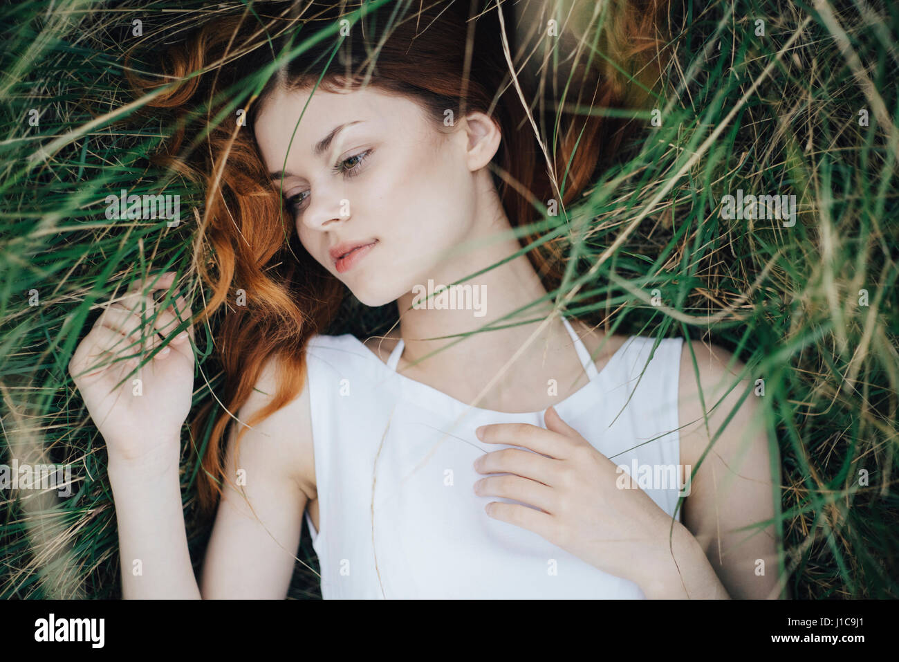 Caucasian woman laying in grass - Stock Image