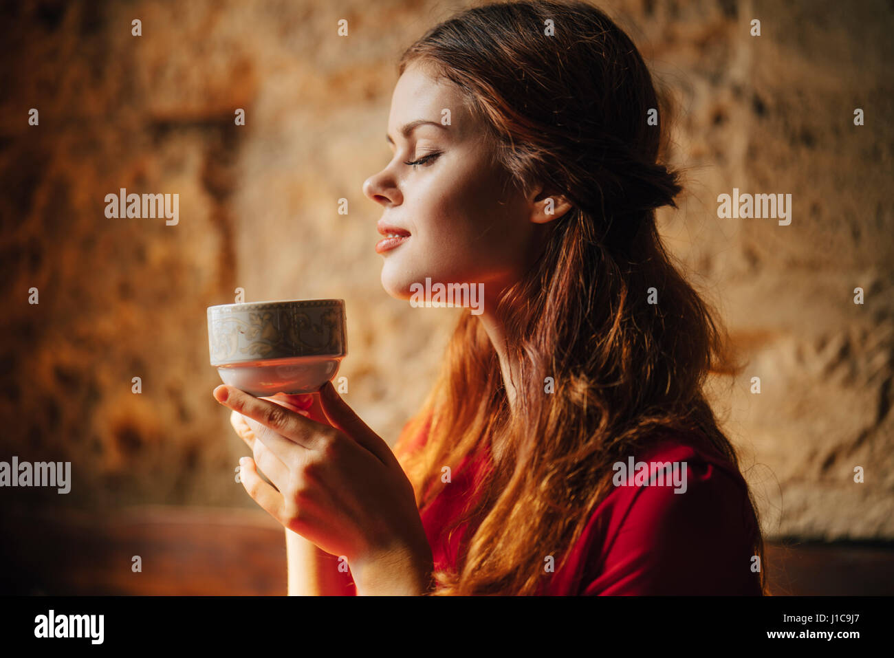 Caucasian woman enjoying aroma of cup of tea - Stock Image