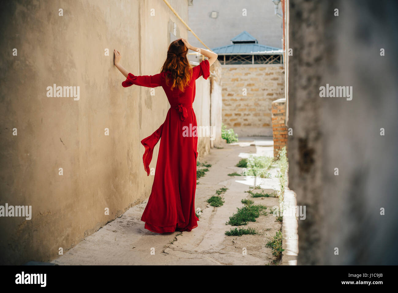 Caucasian woman wearing red dress in alley - Stock Image
