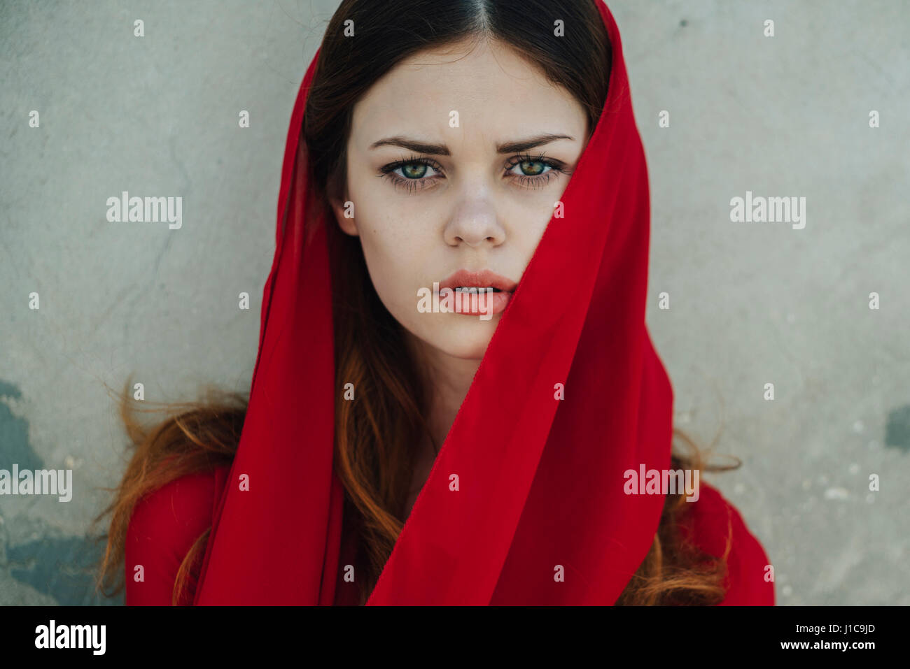 Serious Caucasian woman wearing red headscarf - Stock Image