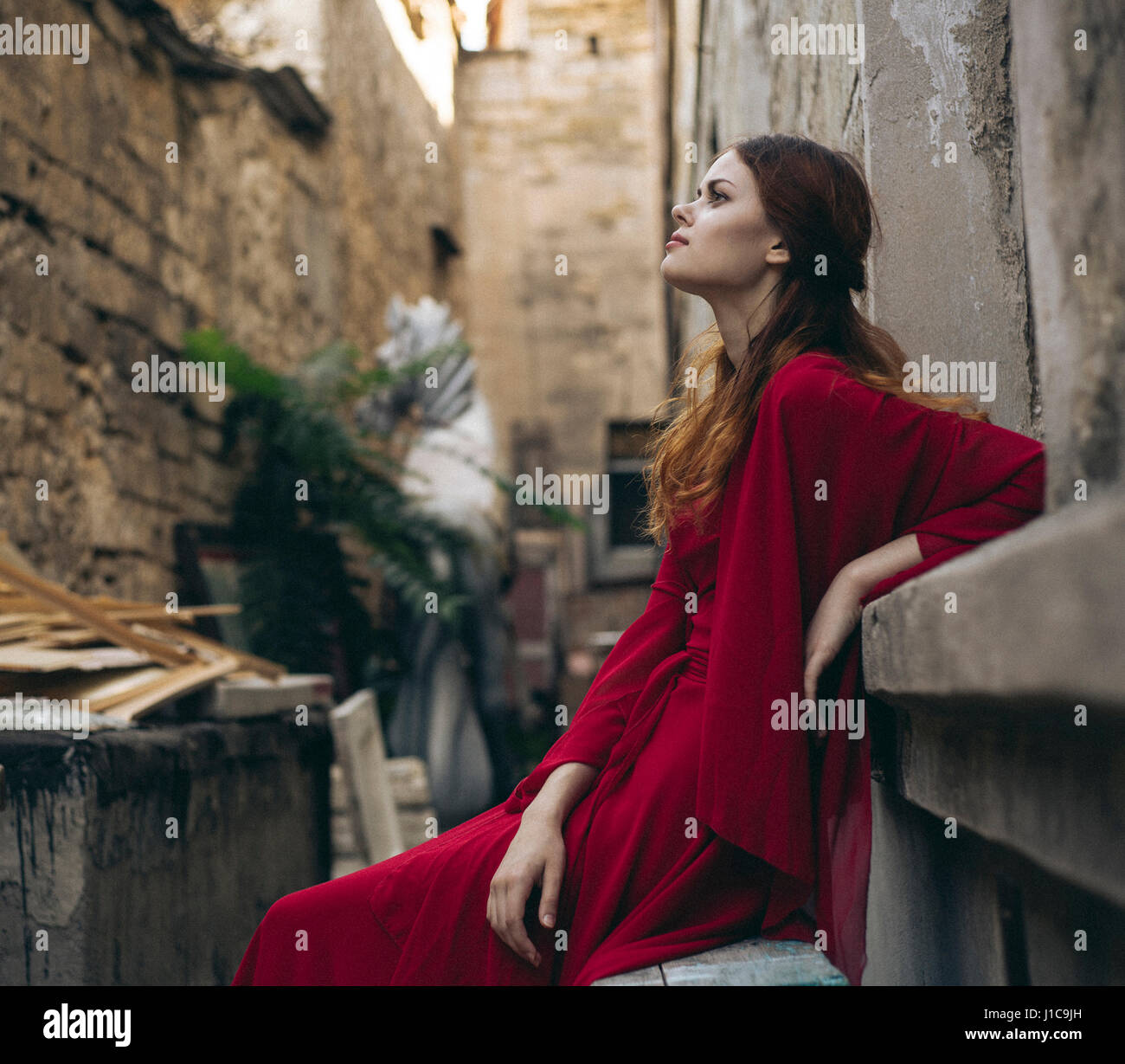 Caucasian woman wearing red dress sitting on bench in alley - Stock Image