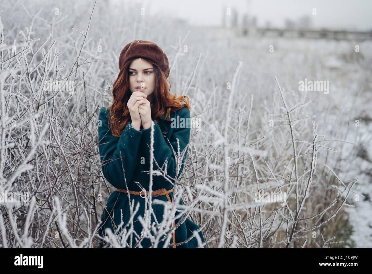 Caucasian woman rubbing hands in winter field - Stock Image