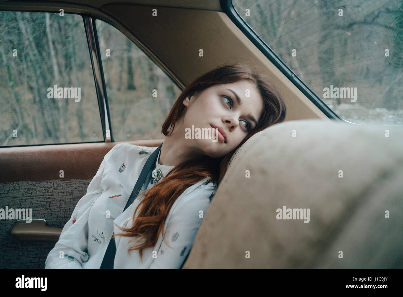Caucasian woman in back seat of car looking out window - Stock Image