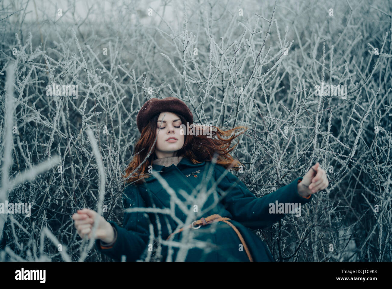 Caucasian woman laying on branches in winter field - Stock Image