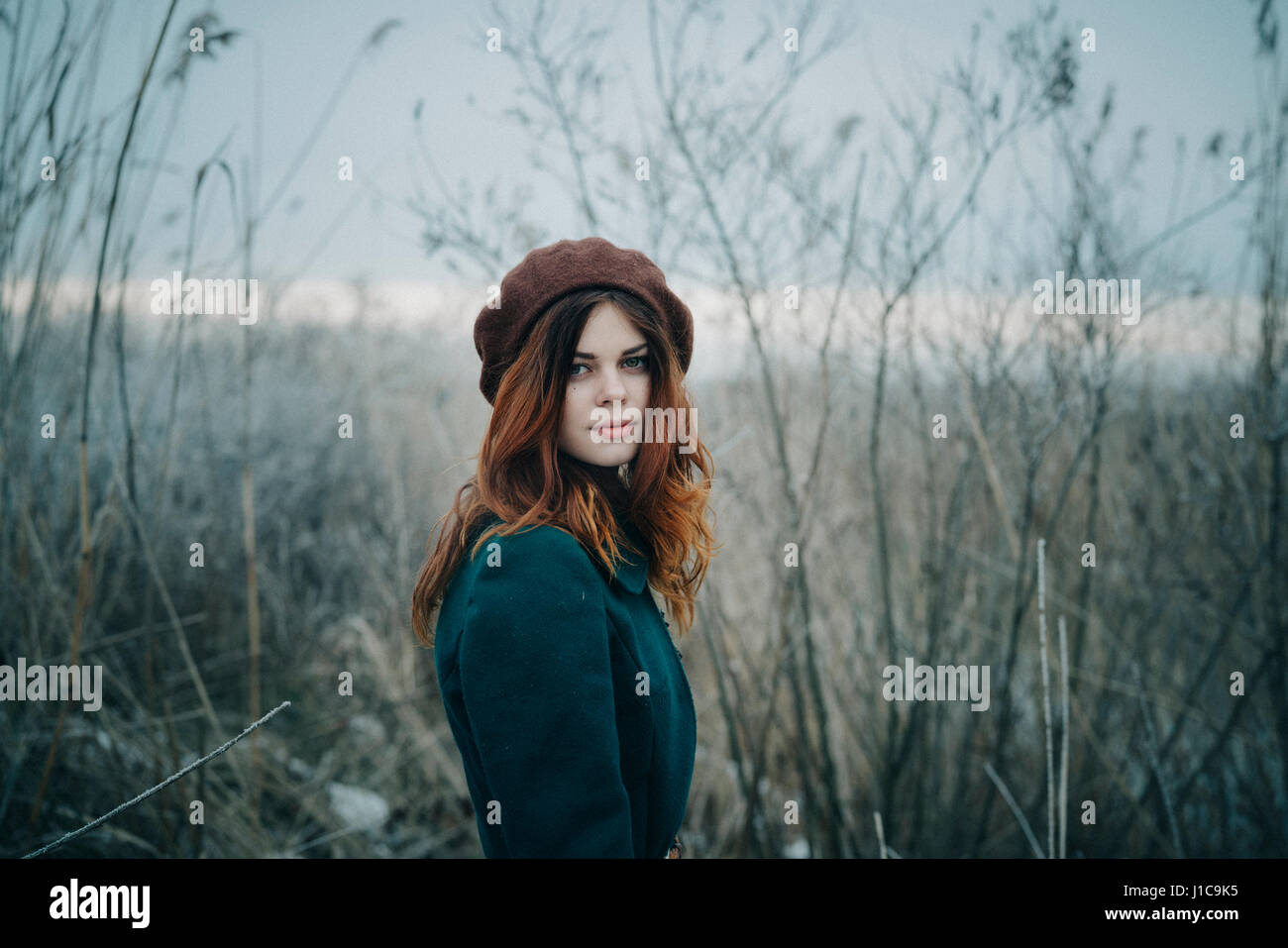 Serious Caucasian woman standing in field - Stock Image