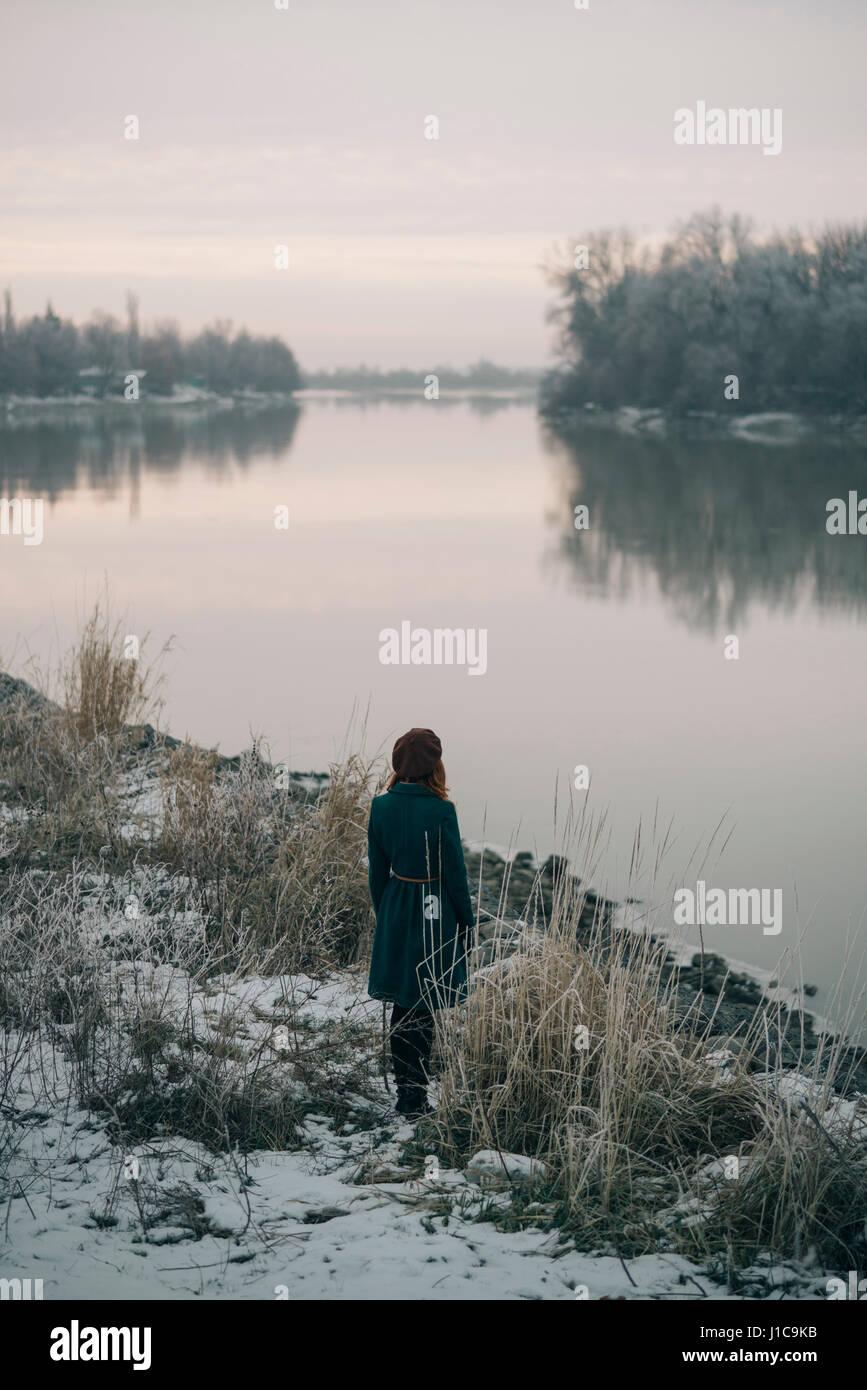 Caucasian woman standing near river in winter - Stock Image