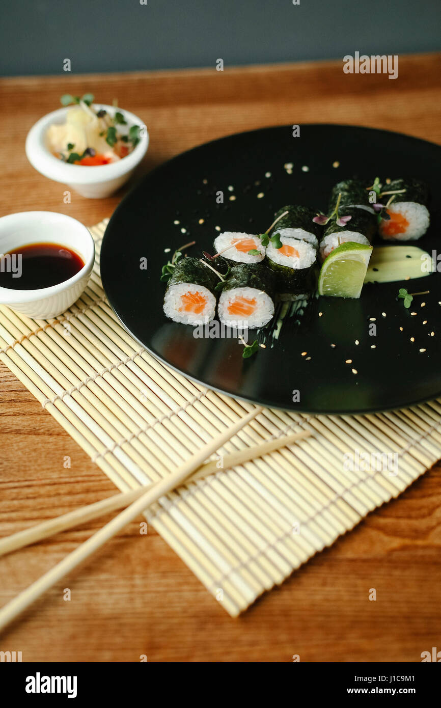 Chopsticks and sushi with sauce - Stock Image