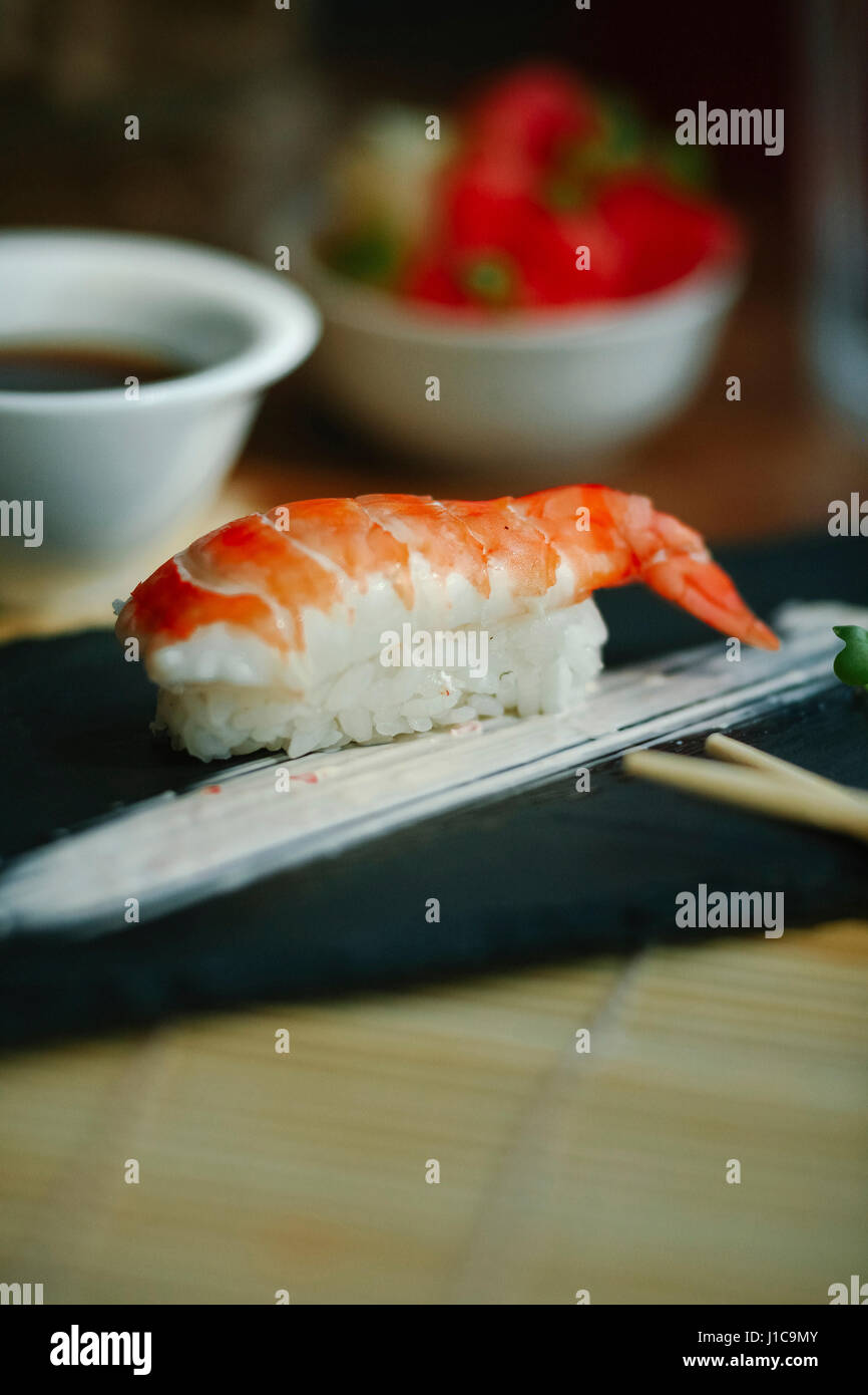 Shrimp on rice with chopsticks - Stock Image