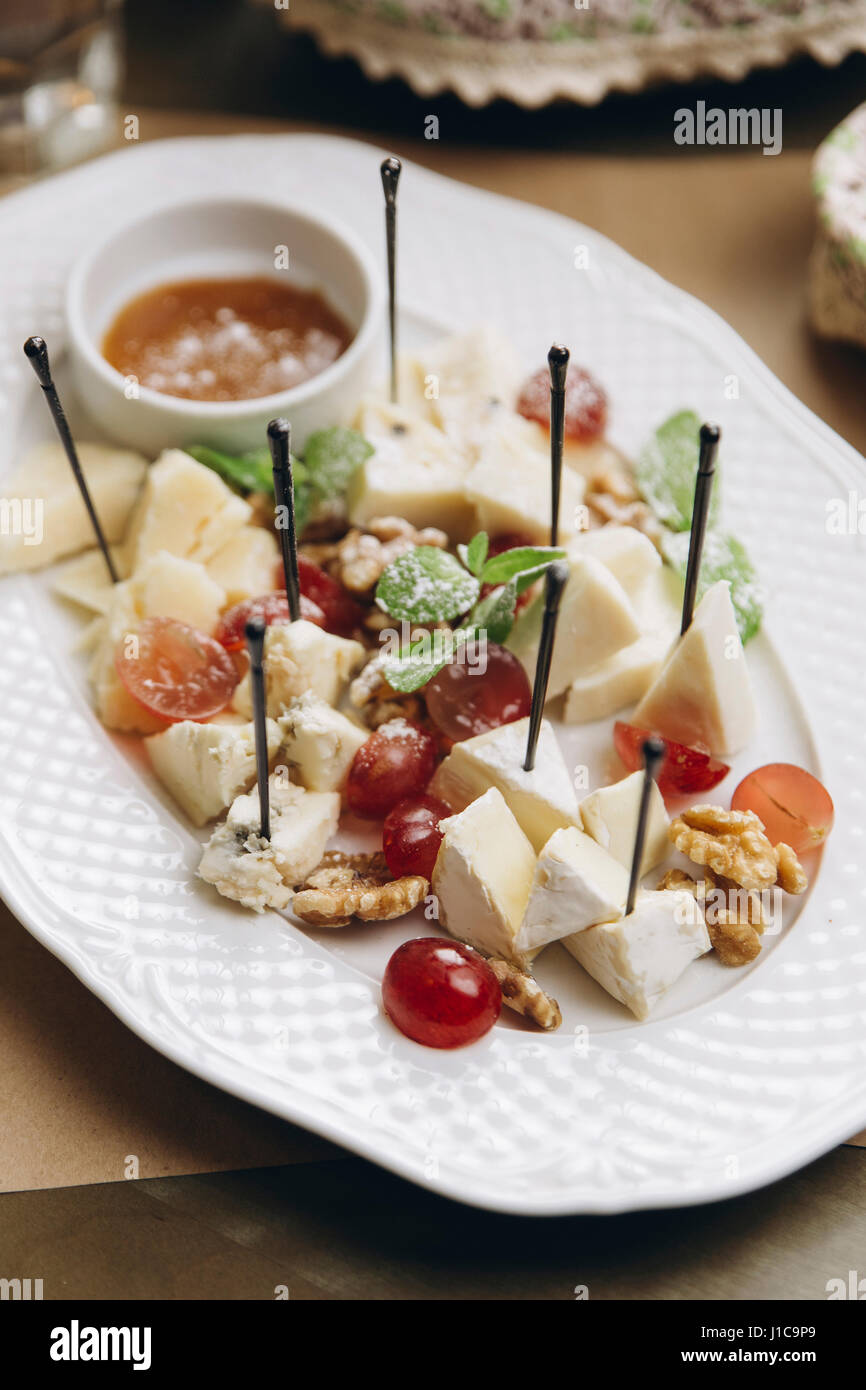 Cheese and fruit on plate - Stock Image