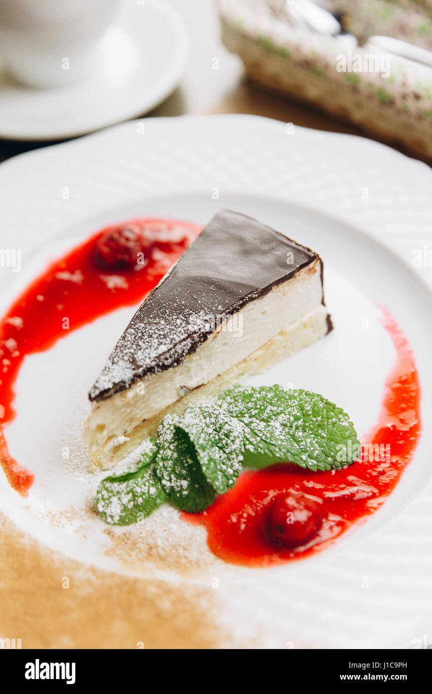 Cheesecake slice on plate with powdered sugar and berry sauce - Stock Image