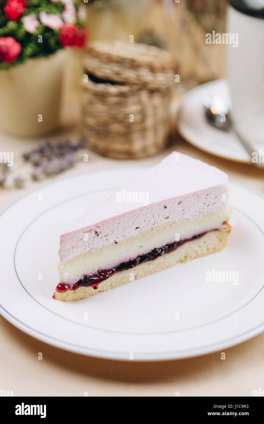 Slice of blackcurrant cheesecake on plate - Stock Image