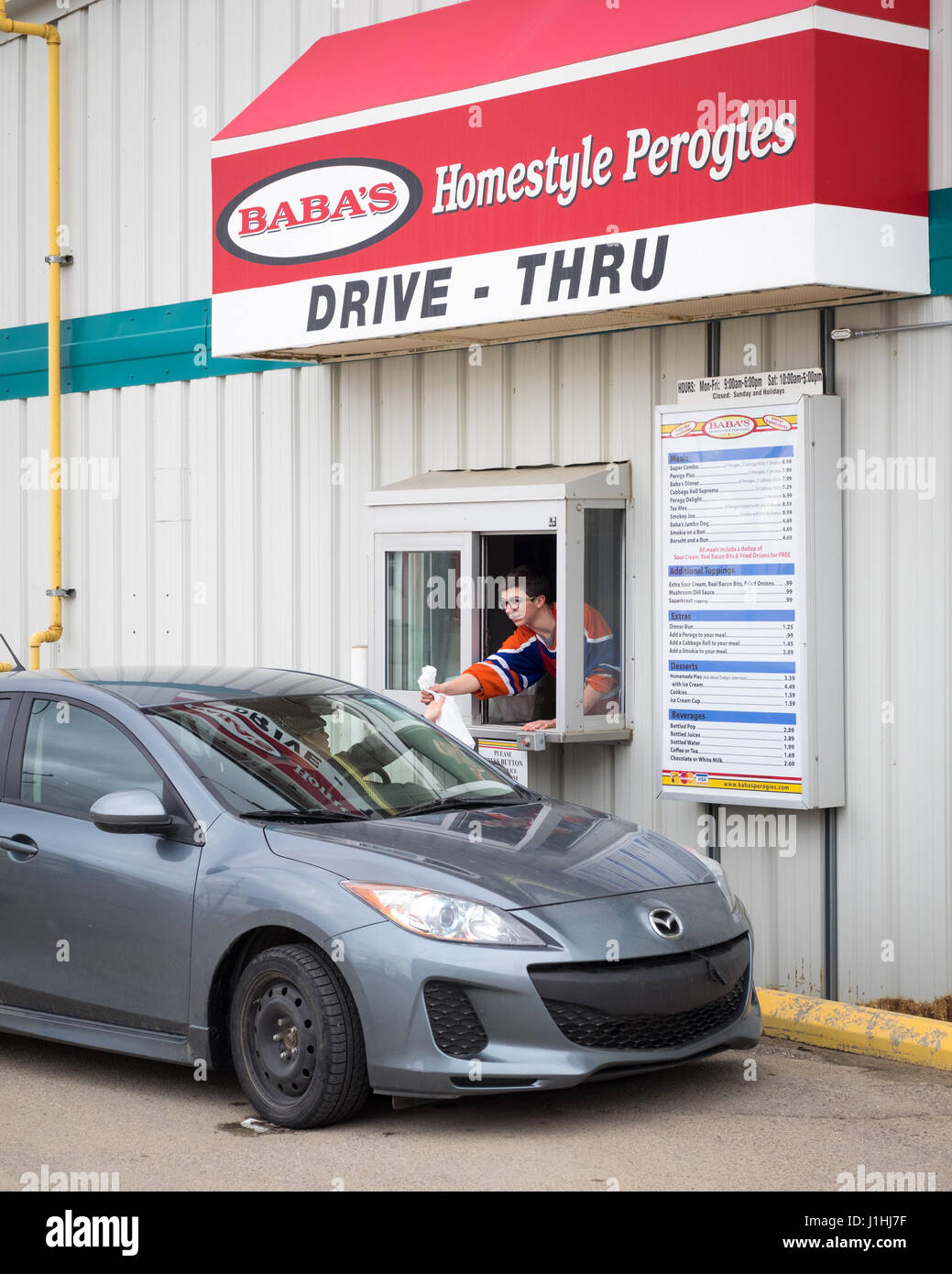 A drive-thru customer at the drive-thru window at Baba's Homestyle Perogies in Saskatoon, Saskatchewan, Canada. - Stock Image