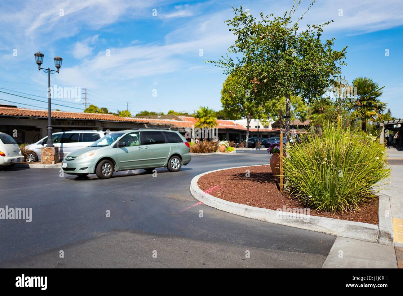 A minivan passes through the parking lot at the Town and Country Shopping Center in the Silicon Valley town of Palo - Stock Image