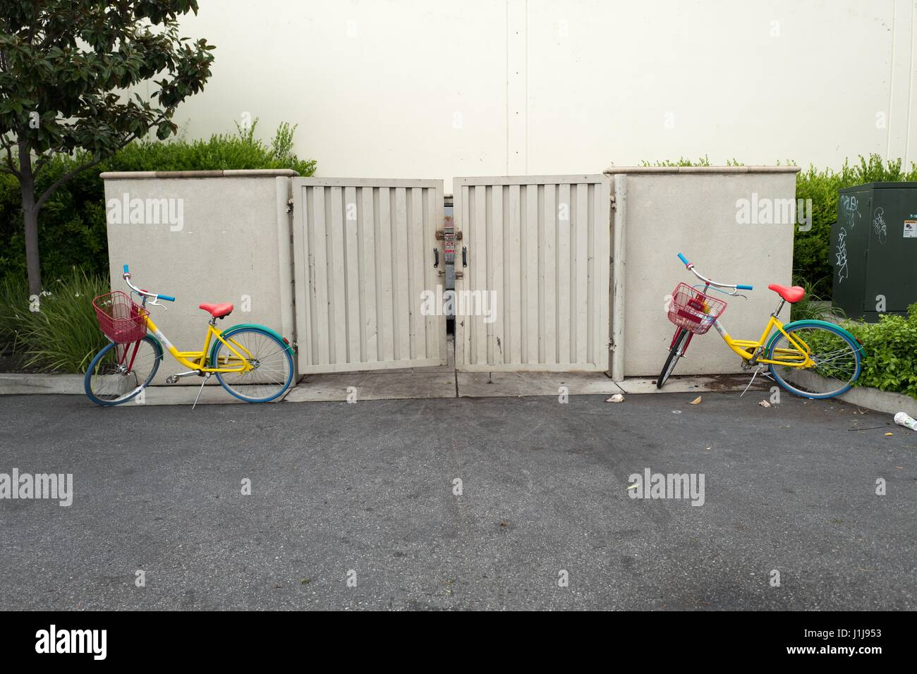 Two Google bikes are haphazardly parked near a garbage dumpster near the Googleplex, the Silicon Valley headquarters - Stock Image
