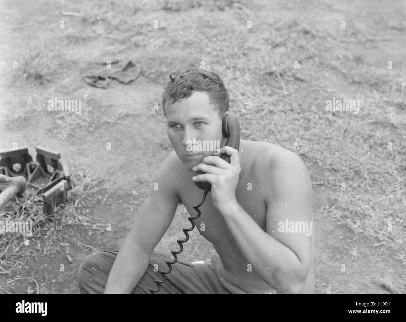 A shirtless United States soldier sits on the ground and speaks on a portable radio during the Vietnam War, Vietnam, - Stock Image