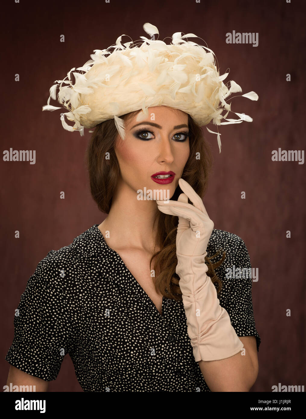Young brunette model in a vintage white feathered hat - Stock Image