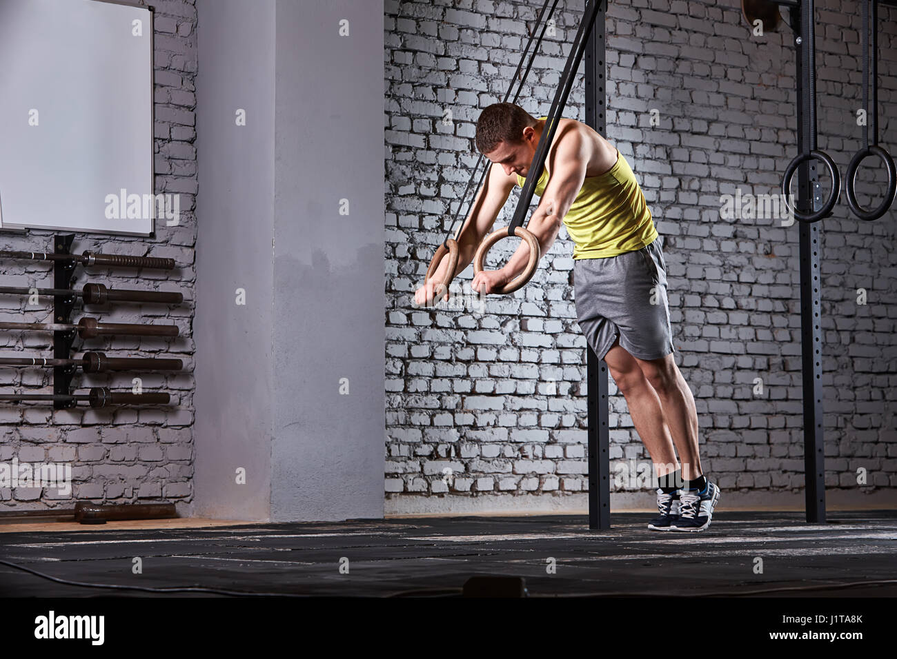 Young athletic man in the sportwear training at the cross fit gym with rings against brick wall. Sportsman in the - Stock-Bilder