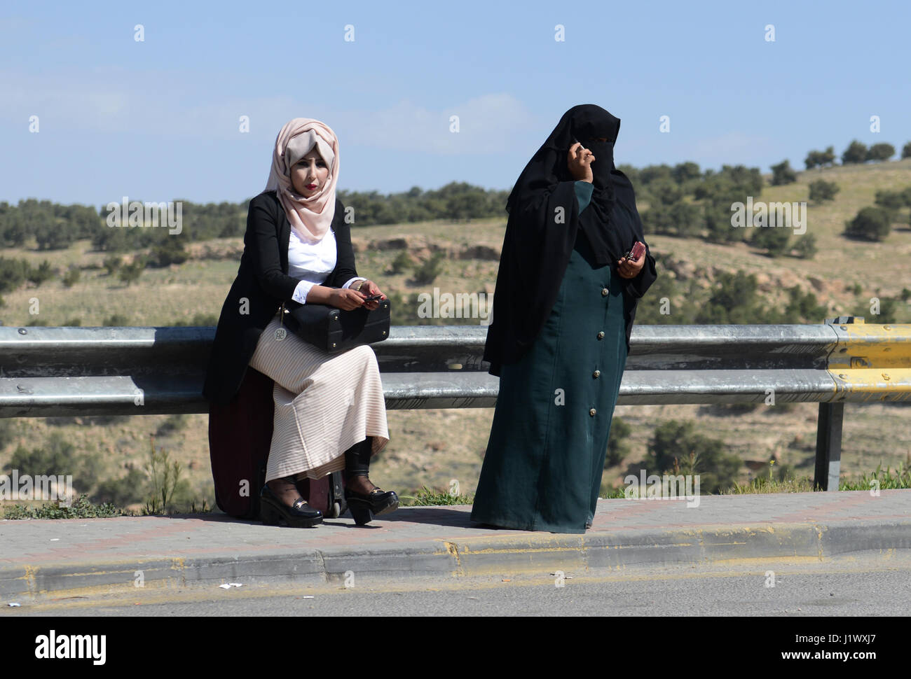 Jordanian women wating for the bus in a rural area in northern Jordan. - Stock Image