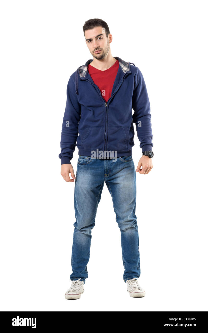 Tense young casual man in blue hooded sweatshirt looking at camera skeptically. Full body length portrait isolated - Stock Image