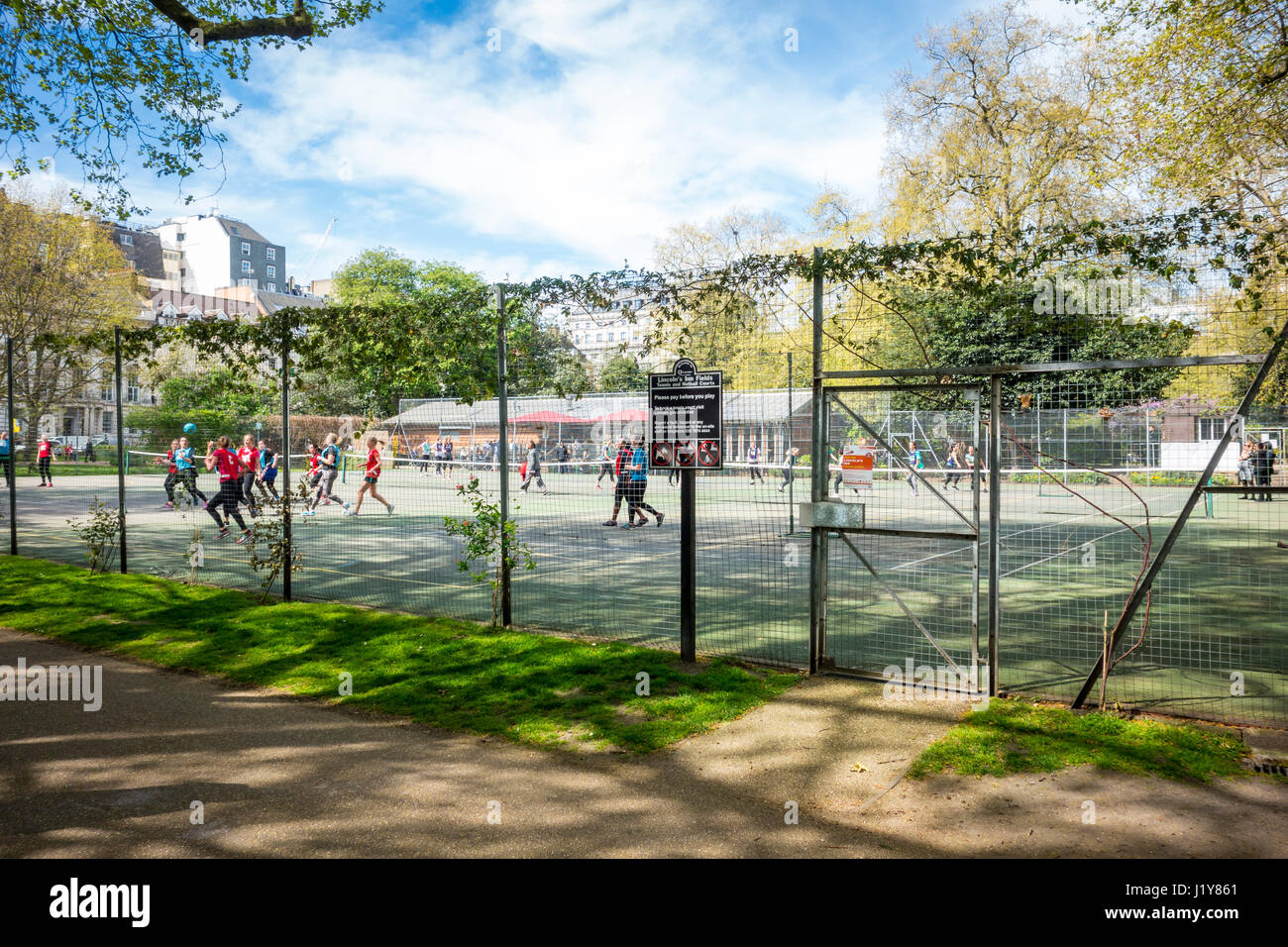 People playing games at Lincoln's Inn Fields tennis and netball courts. London, UK - Stock Image
