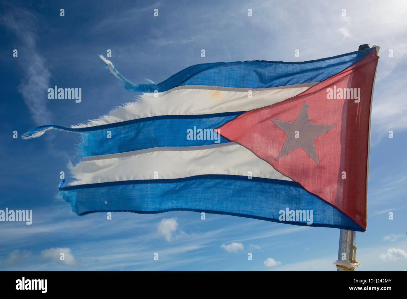 The Flag of Cuba, consisting of five strobes and a red equilateral triangle  with a white five-pointed star. - Stock-Bilder