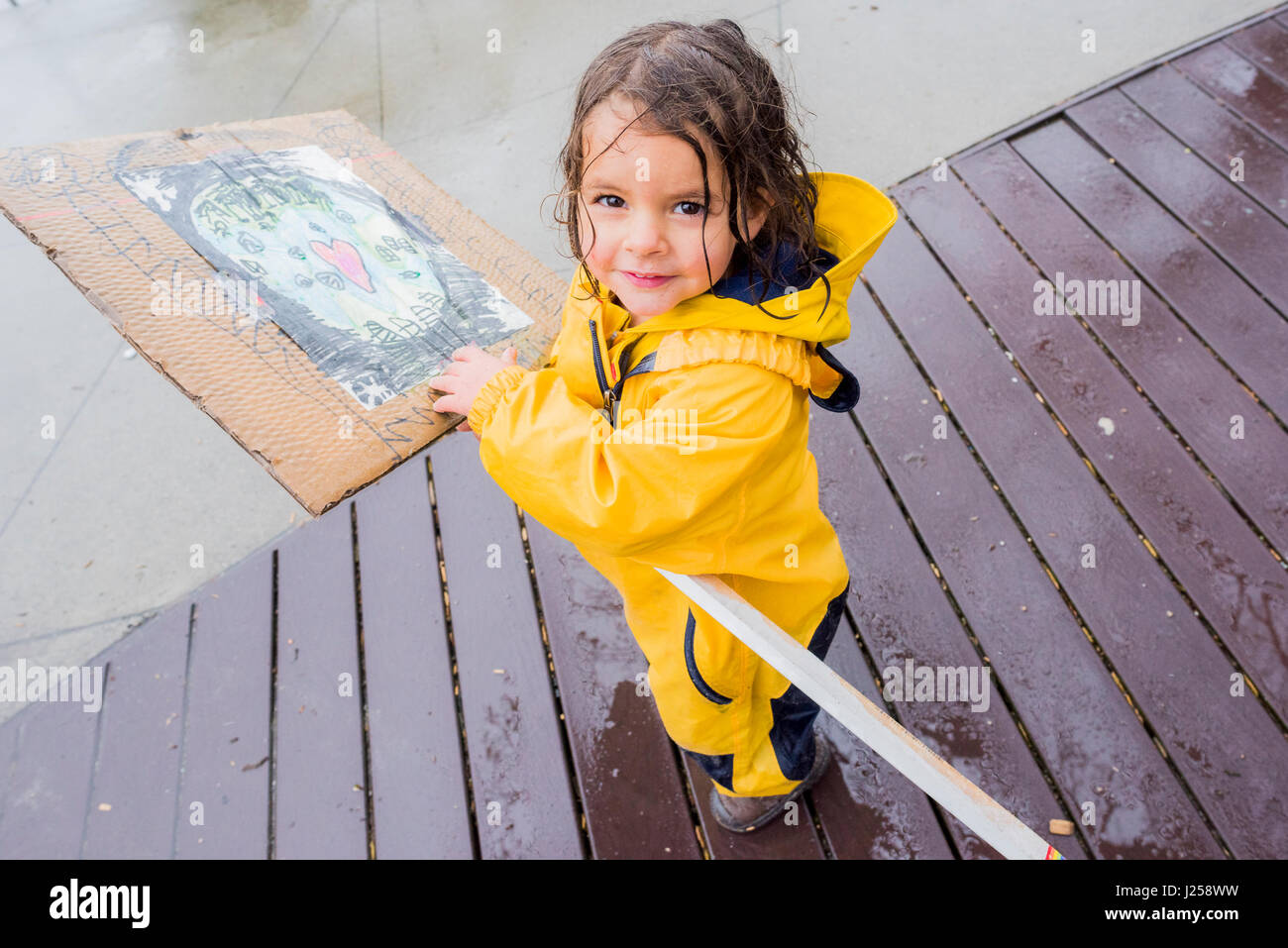 Young girl in yellow raincoat with sign  at the Earth Day Parade and Festival, Vancouver, British Columbia, Canada - Stock Image