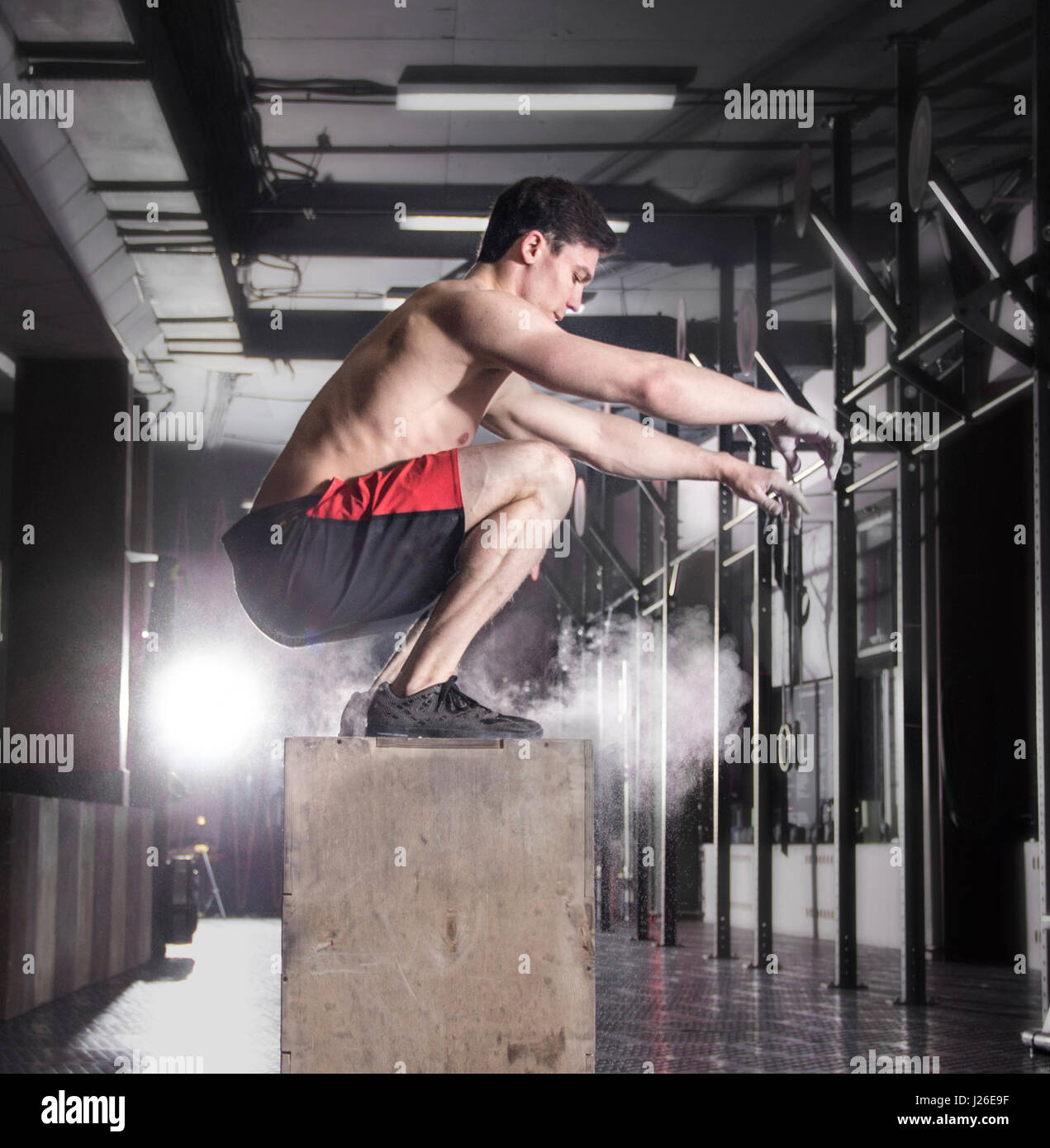 Fit young man box jumping at a crossfit gym.Athlete is performin - Stock-Bilder