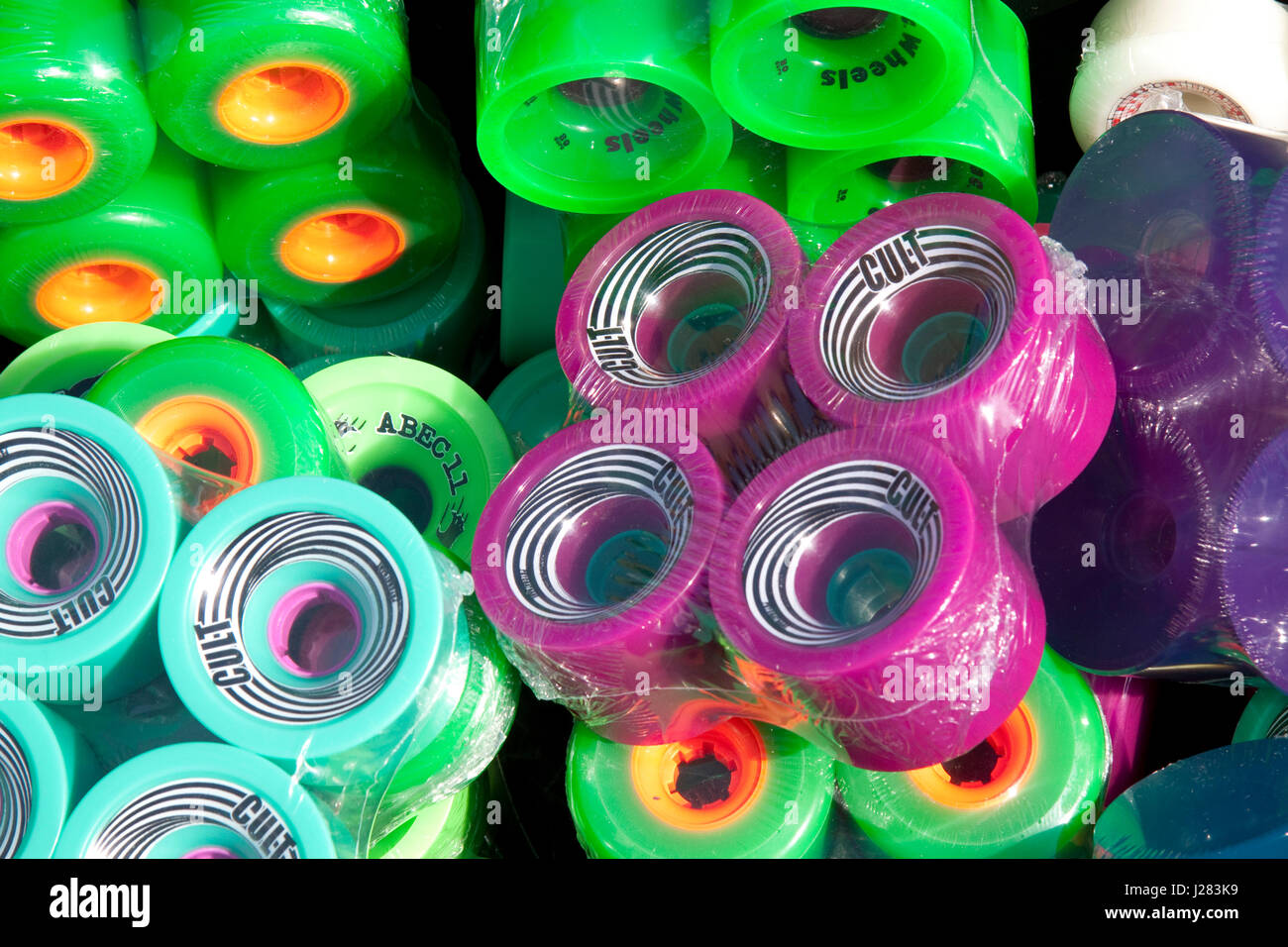 Brightly coloured/colored packs of skateboard wheels - Stock Image
