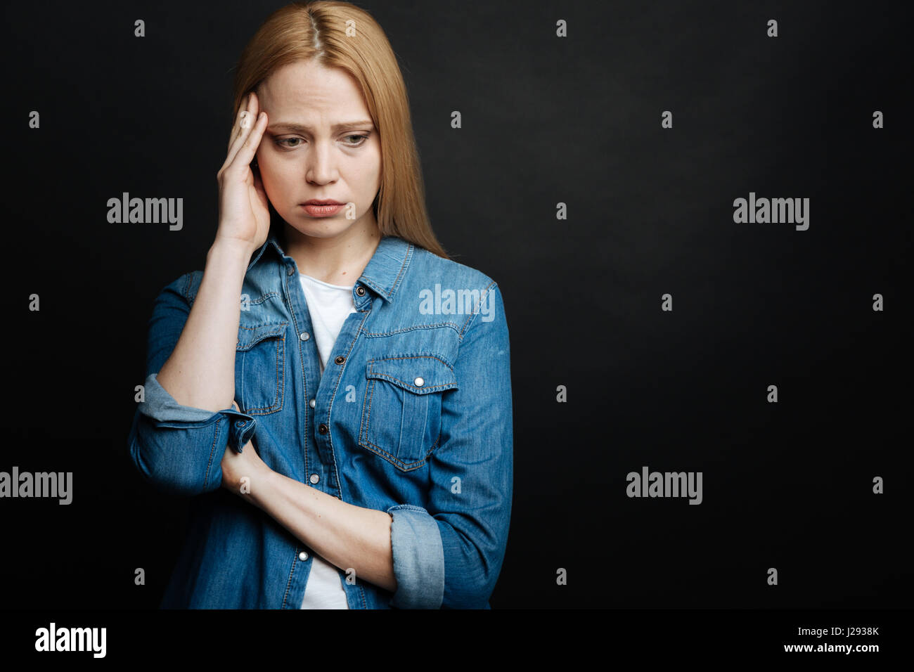 Pity young woman feeling depressed in the studio - Stock Image