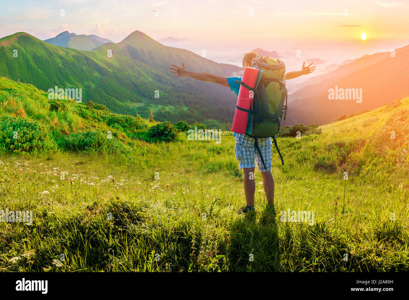 Hiker with a backpack standing in mountains. Amazing nature landscape. Soft light effect - Stock-Bilder