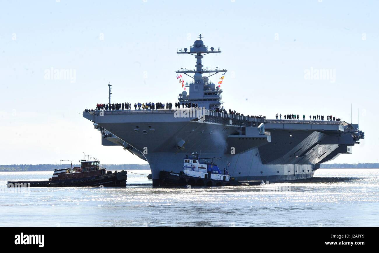 U.S. sailors man the rails as the U.S. Navy Gerald R. Ford-class aircraft carrier USS Gerald R. Ford departs Huntington - Stock Image