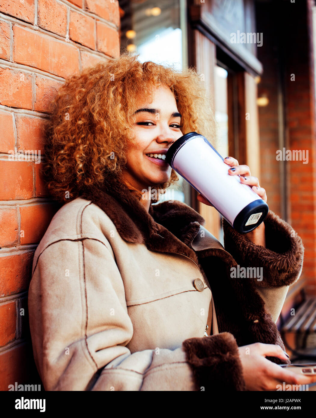 young pretty african american women drinking coffee outside in cafe, modern real business woman lifestyle concept - Stock Image