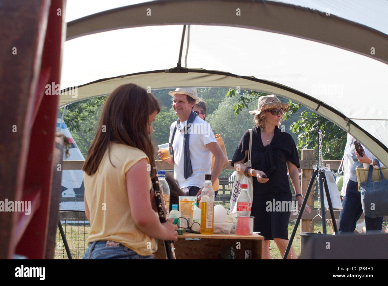 At the Maverick music festival people pass by an open tent - Stock Image