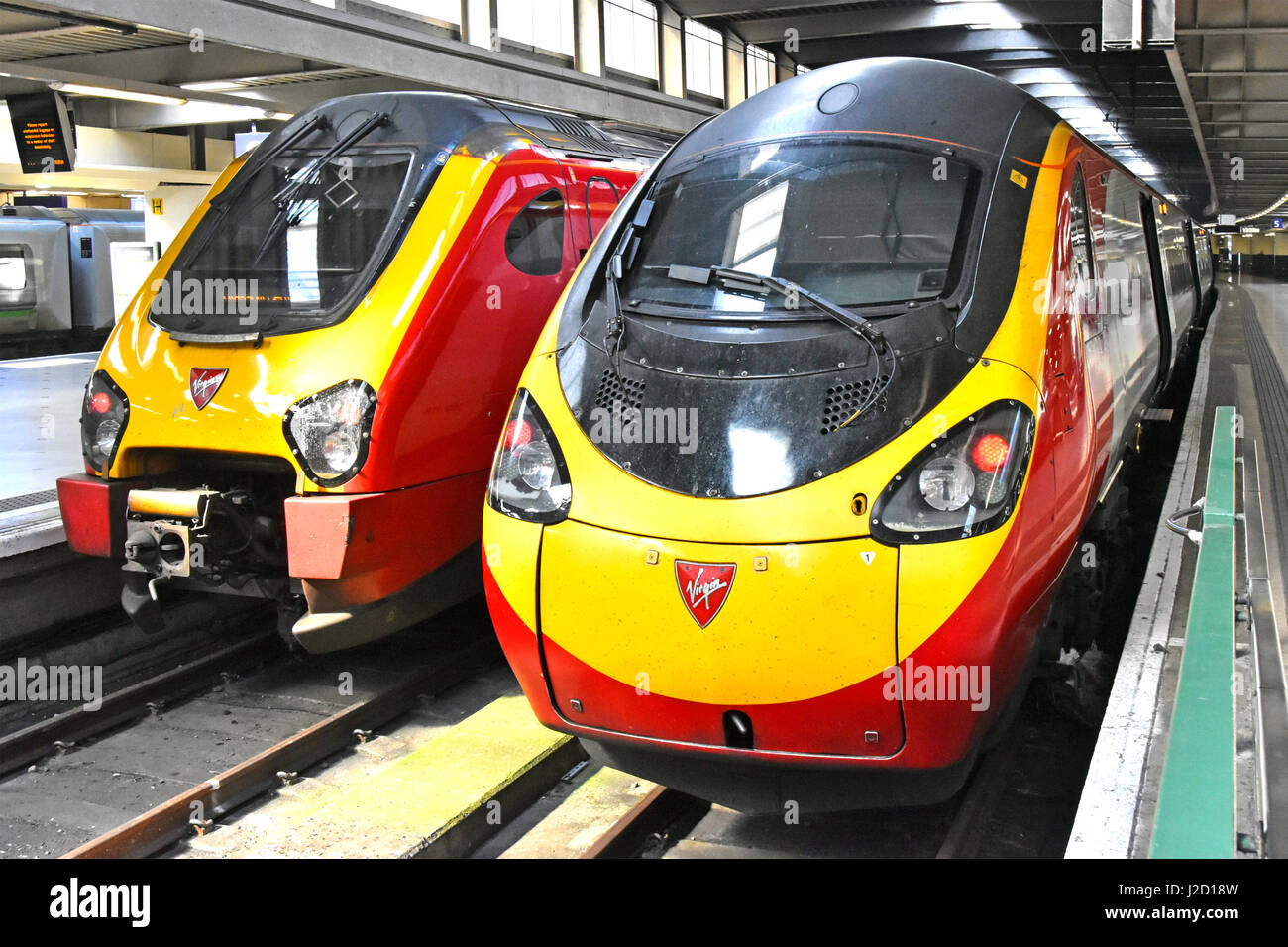 Two streamlined Virgin train units operated by Virgin Trains at Euston railway station platforms London England - Stock Image