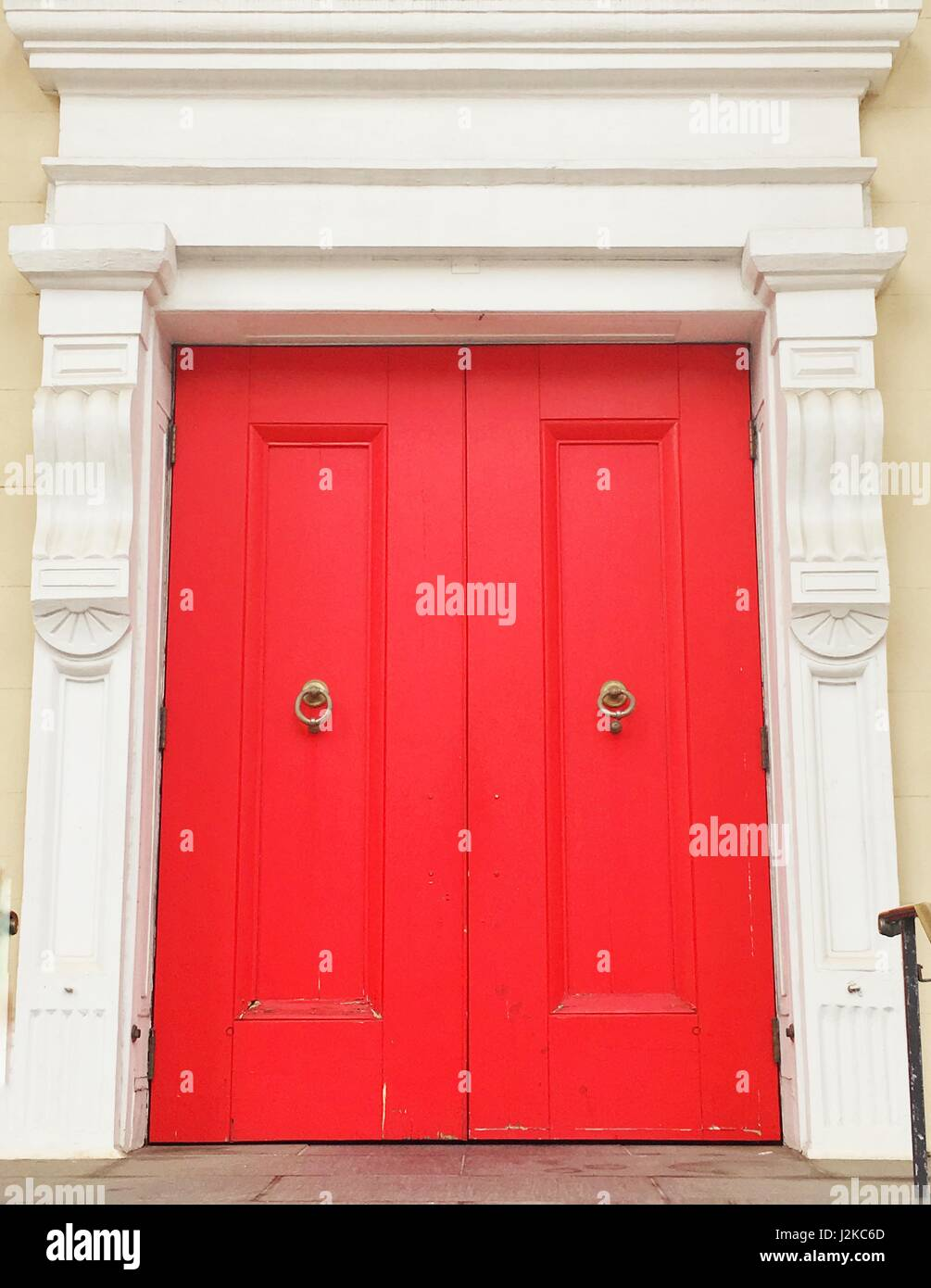 Red double doors on a white building. - Stock Image