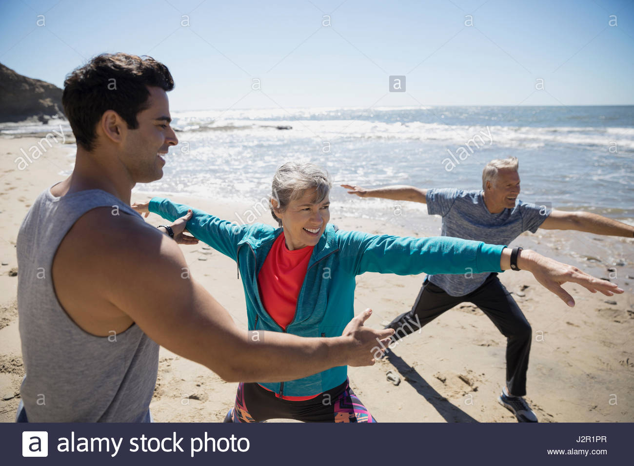 Crossfit trainer helping senior couple exercising, practicing yoga warrior 2 pose on sunny beach - Stock-Bilder