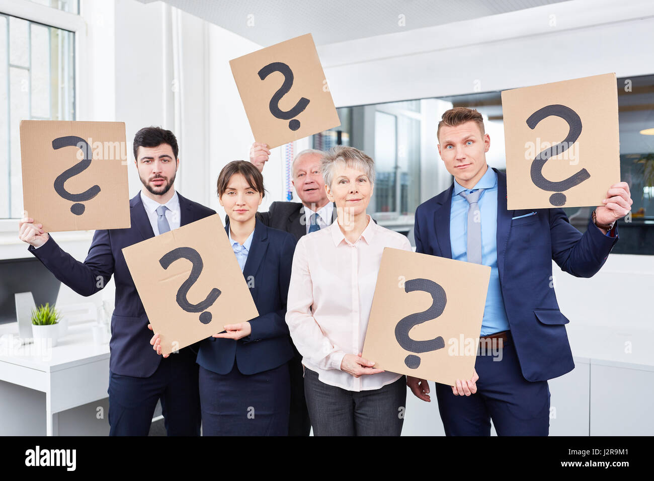 Business team holds question marks for doubt - Stock Image