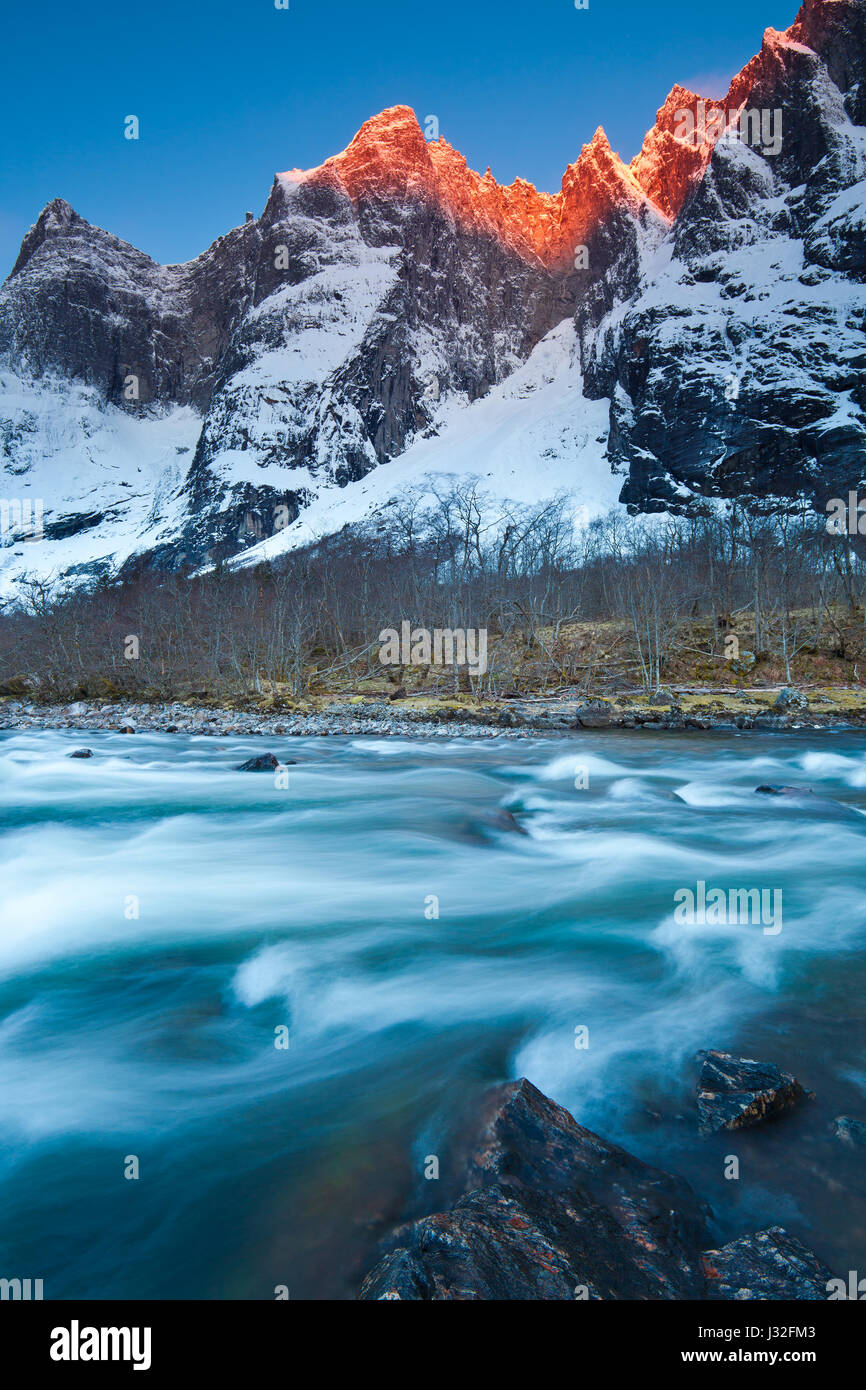 First light on the 3000 feet vertical Troll Wall and the peaks Trolltindane in the Romsdalen valley, Norway. River - Stock-Bilder