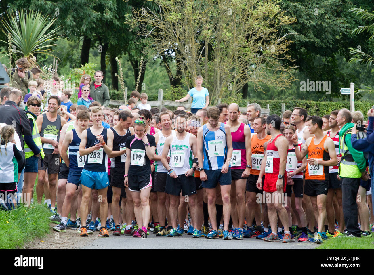 Runners wait for the start of a road race - Stock Image