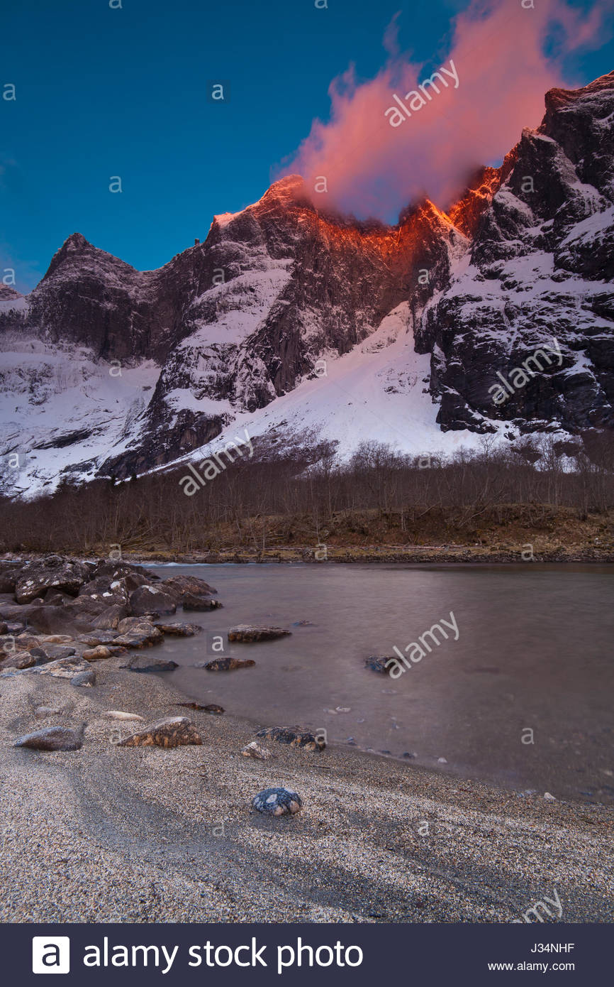 First light on the 3000 feet vertical Troll Wall and the peaks Trolltindane in Romsdalen valley, Norway. River Rauma - Stock-Bilder