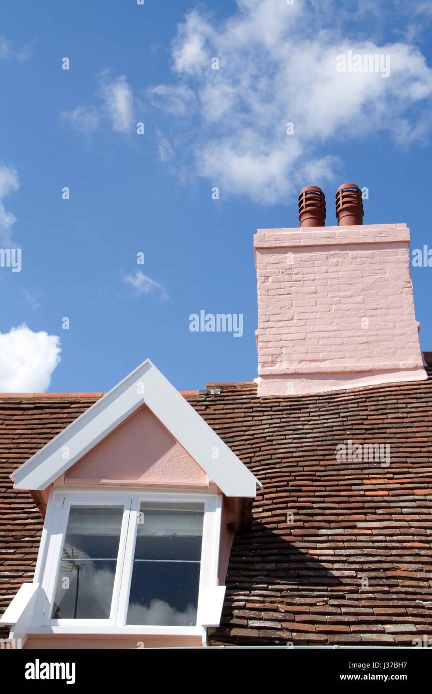 Period chimneys and gable windows against a blue sky - Stock Image