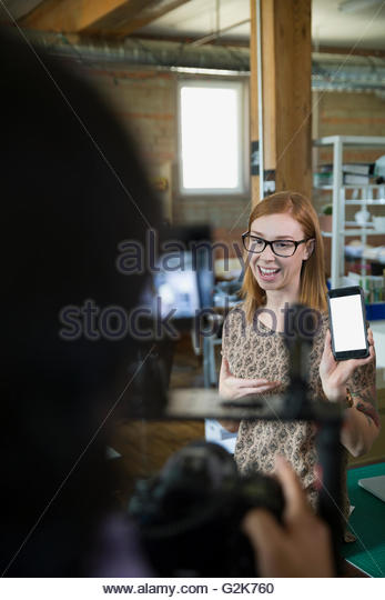 Cameraman filming creative businesswoman for tutorial - Stock Image