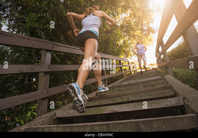 Mid adult man and young woman running up steps, rear, low angle view - Stock Image