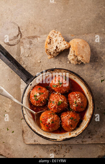 Meatballs cooked in tomato sauce in pan on grey backround - Stock Image