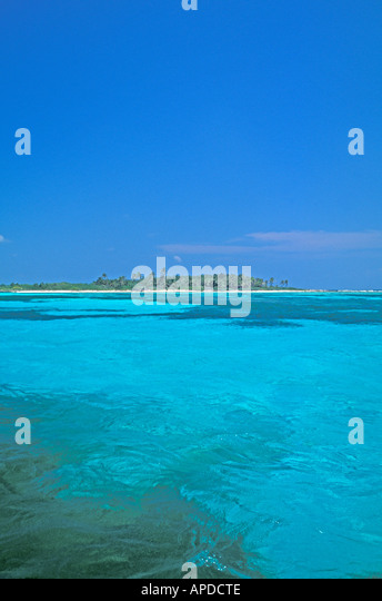 Deserted tropical island surrounded by clear water - Stock Image