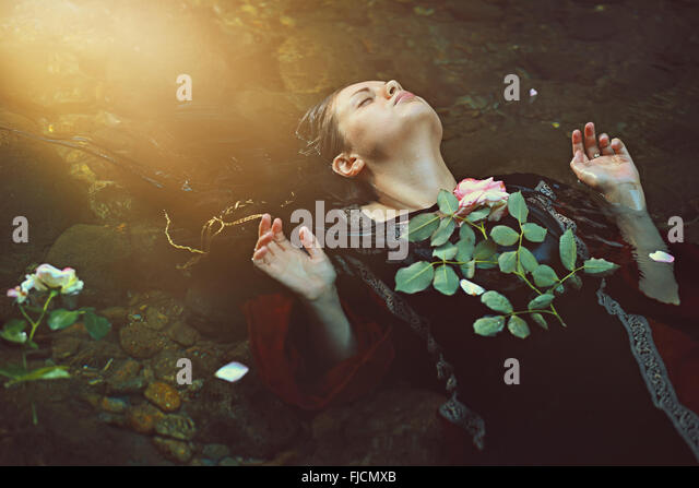 Woman in dark water stream and soft sunlight . Romantic and tragedy - Stock-Bilder