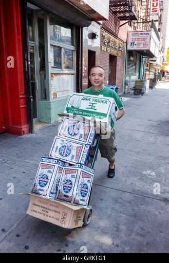 Lower Manhattan New York City NYC NY Chinatown Allen Street Chinese Asian man delivery man job dolly box pushing - Stock Image