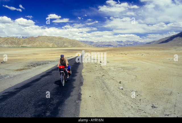Cyclist wearing head covering riding fully-loaded bike down a lonely stretch of desert highway, Ladakh, India - Stock-Bilder