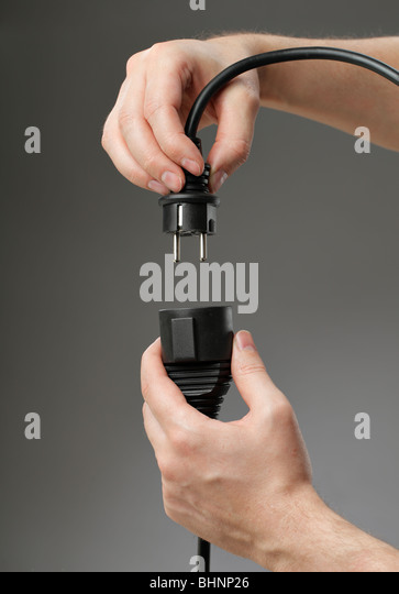Hand plugging a black european extension cord - Stock Image